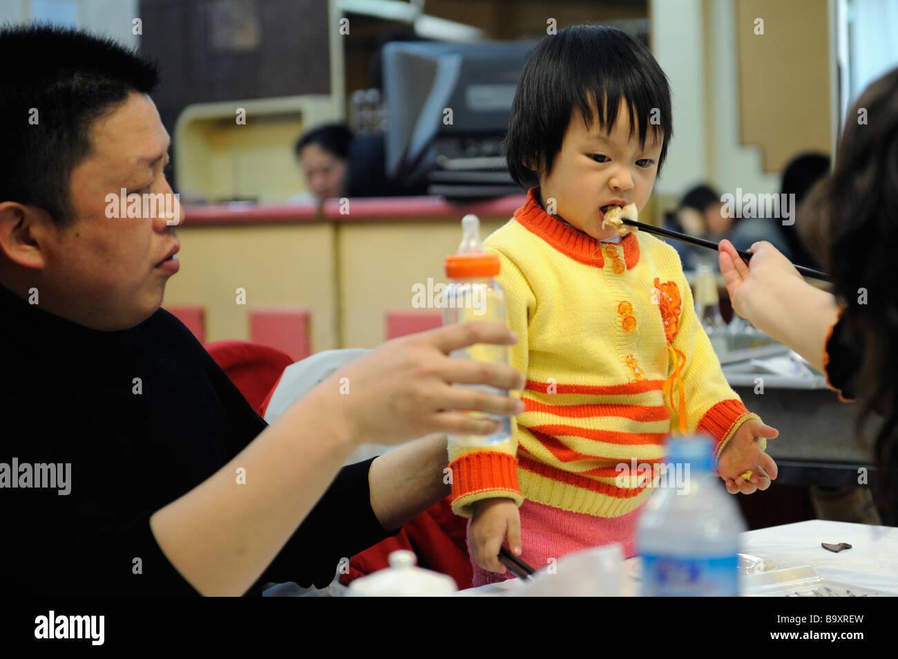 Chinesisches Ehepaar Fütterung ein Baby in einem Restaurant in Tianjin, China. 14. März 2009 Stockbild