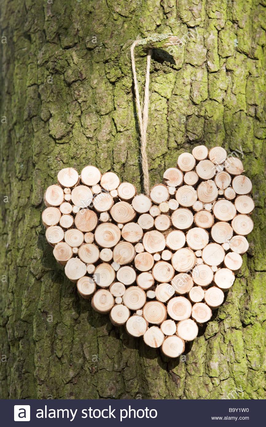 Eine Dekoration aus Holz an einem Baum hängen in Herzform Stockbild