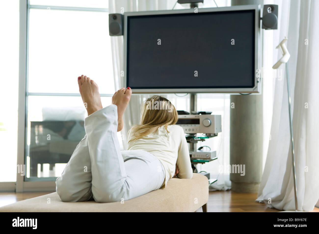 Frau liegend auf Bauch vor dem Flachbild-Fernseher, Rückansicht Stockbild