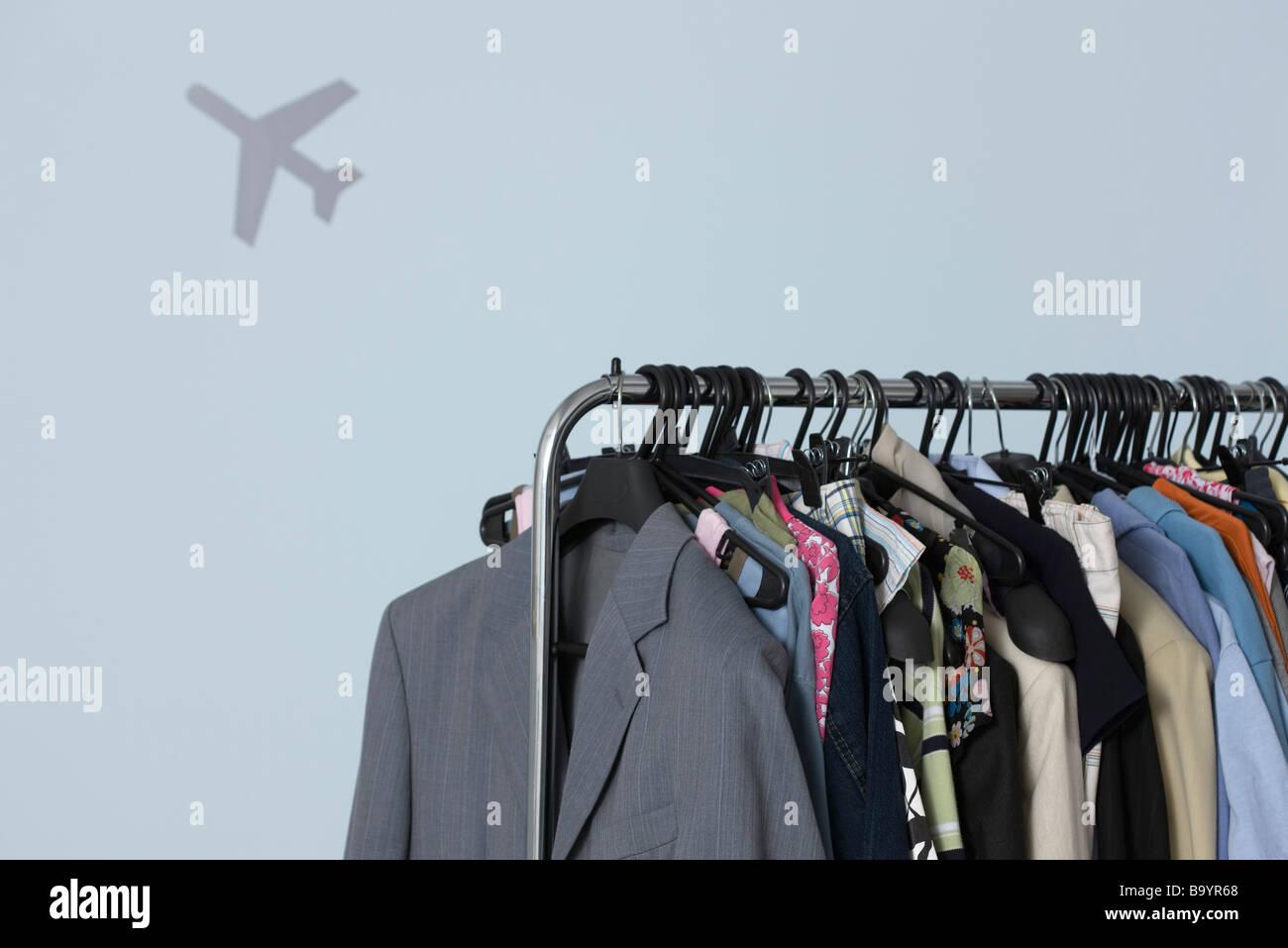 Rack mit Kleidung, Flugzeug-Form im Hintergrund Stockbild