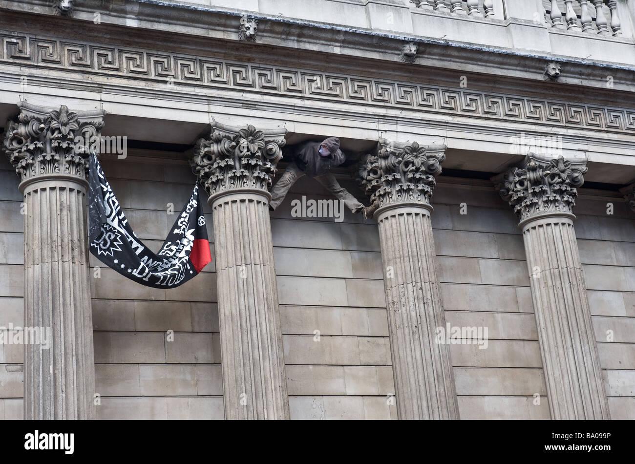 Maskierte Demonstranten klettern die Bank of England auf einer Demonstration in der City of London. Stockbild