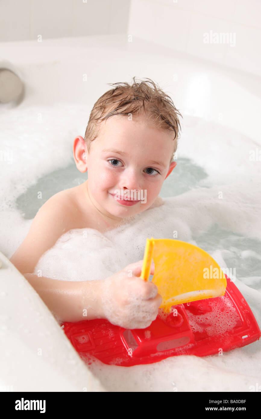 Kleiner Junge in Badewanne mit Spielzeug Segelboot Stockbild