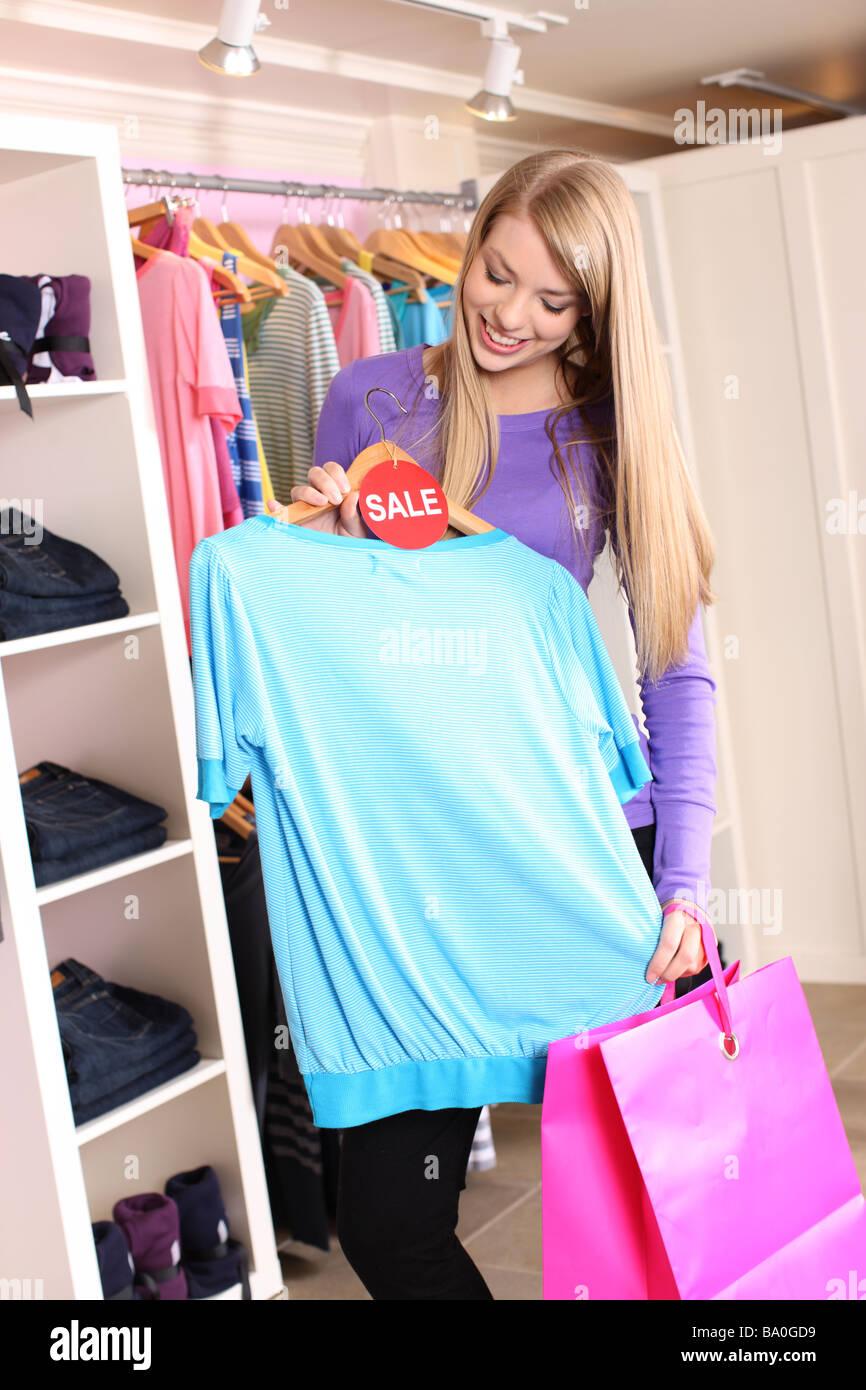 Teenager Shopper schaut Shirt mit Verkauf-tag Stockbild