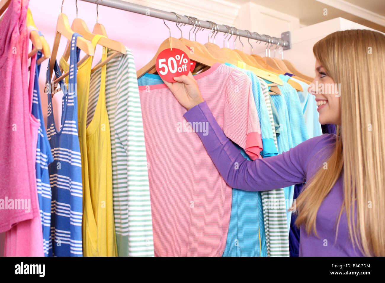 Junge Frau, die Kleidung mit Verkauf Tag betrachten Stockbild