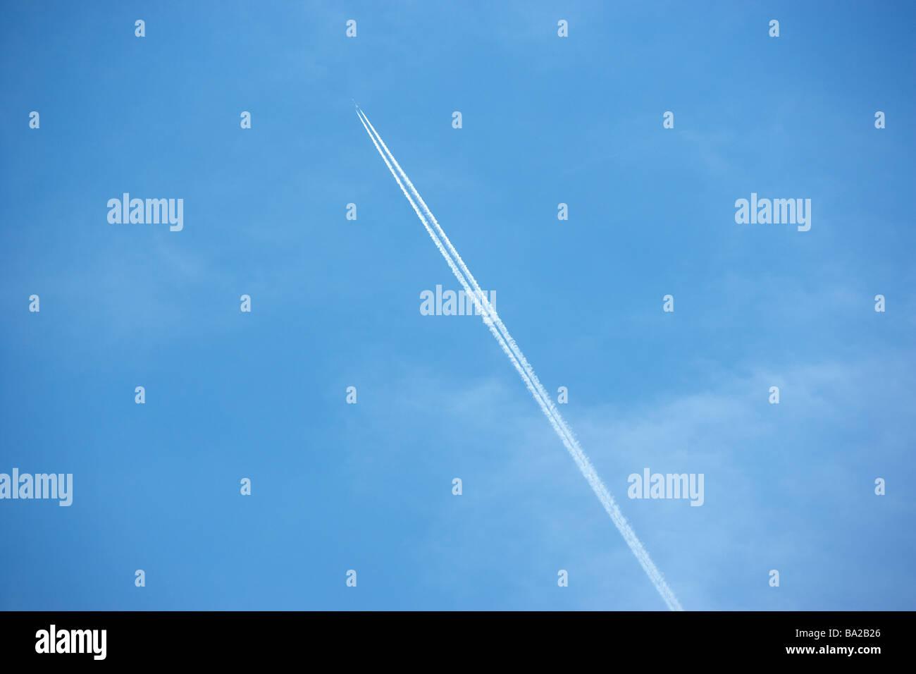 Weiße Kondensation Trail von einem Jet als es fliegen über einen blauen Himmel Stockbild