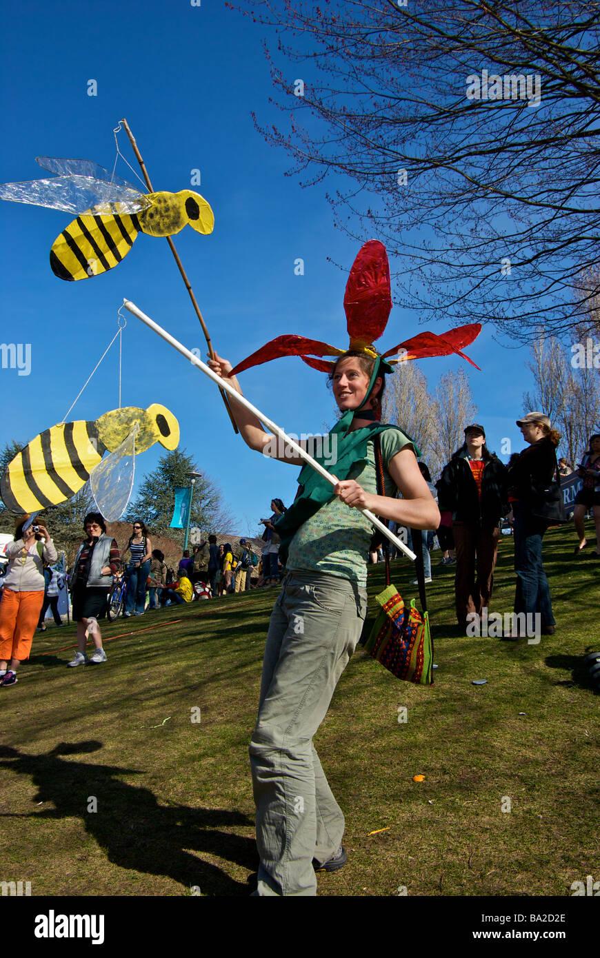 Demonstrant in Blume Kostüm mit Bienen besuchen die Farm zu retten Protest marschieren auf Campus der University Stockbild