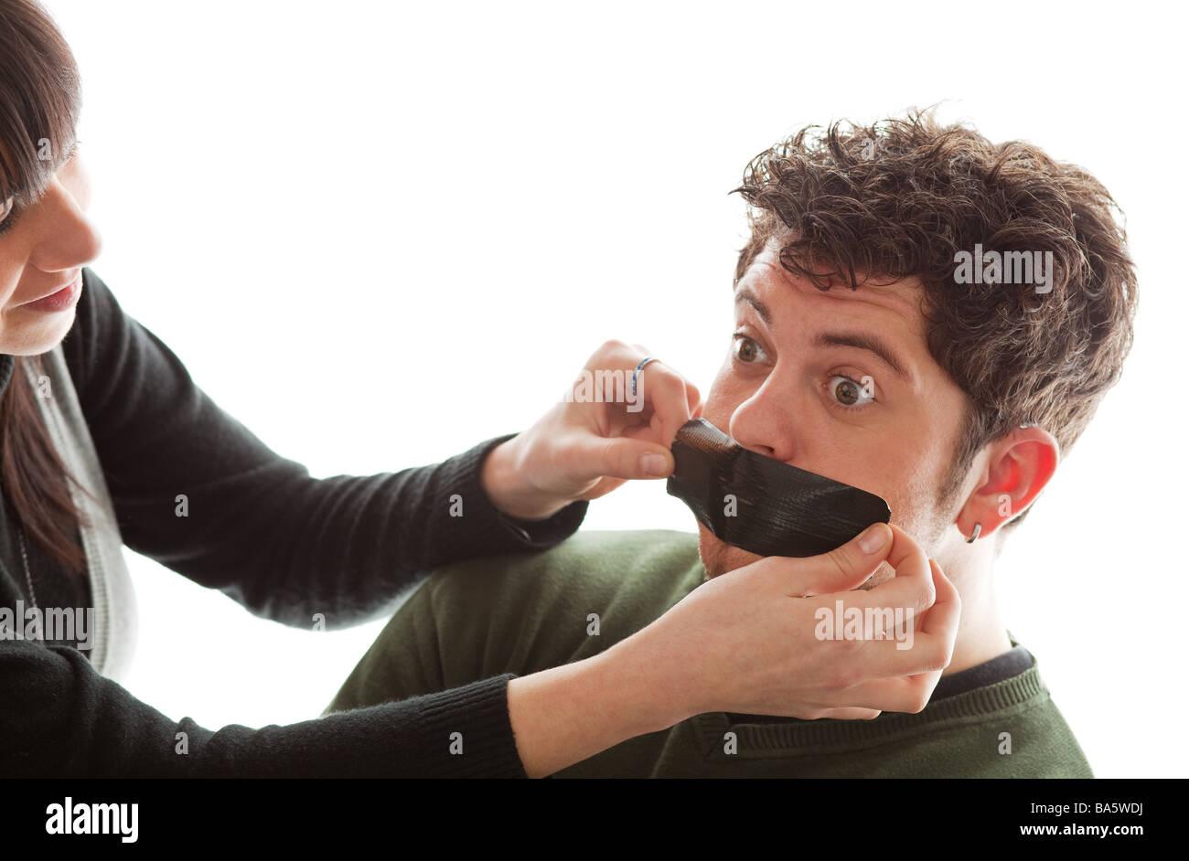 Mädchen jungen Mann s Mund ein Stück Gaffer-Tape aufkleben Stockfoto ...