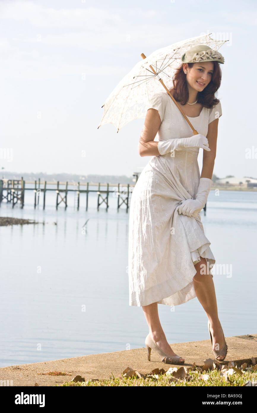 Elegante Dame im weißen Kleid Holding Sonnenschirm am Wasserrand auf ...