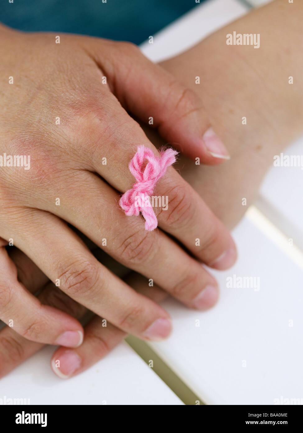 Eine Hand mit einem rosa Faden um einen Finger zu merken, Schweden gebunden. Stockbild