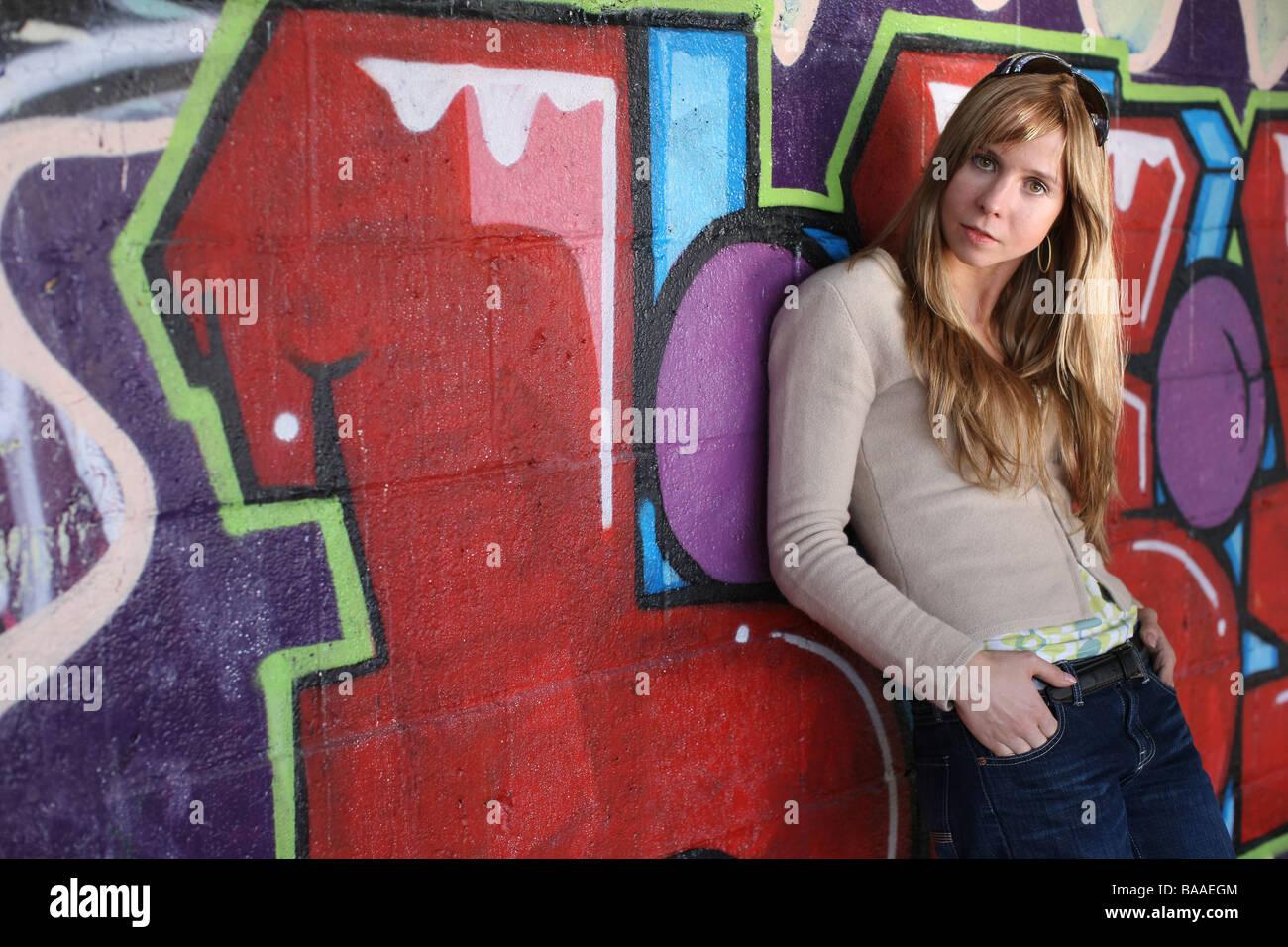Drei Viertel Länge des Mädchens von Graffitiwand Stockbild