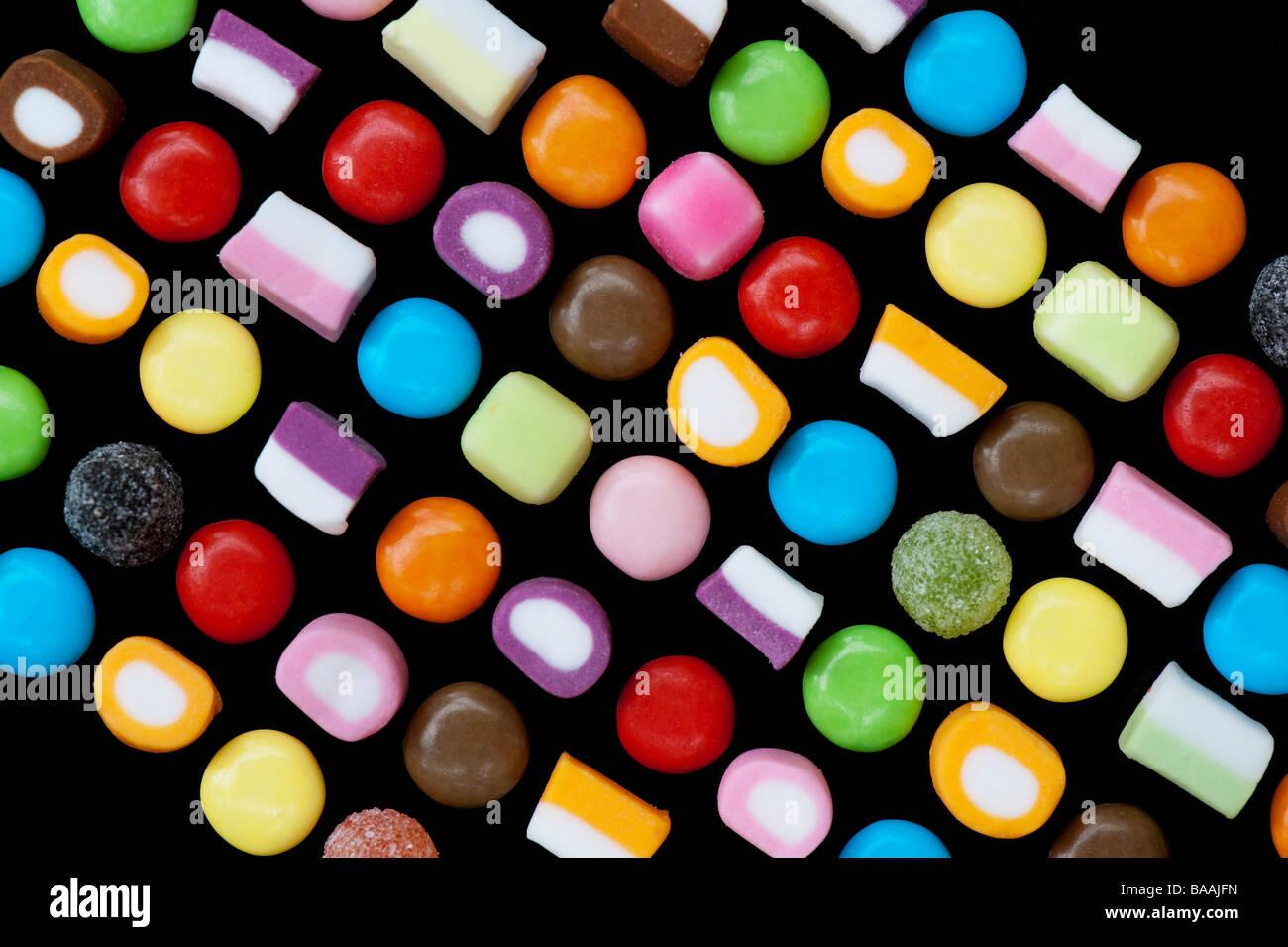 Mehrfarbige dolly Mischungen und smarties Süßigkeiten Muster auf Schwarz Stockbild