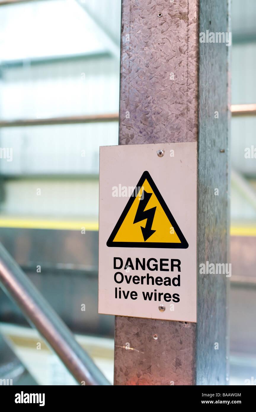 Gelbes Dreieck Arbeitsschutz unterschreiben Warnung vor Gefahr overhead live elektrische Leitungen Stockfoto