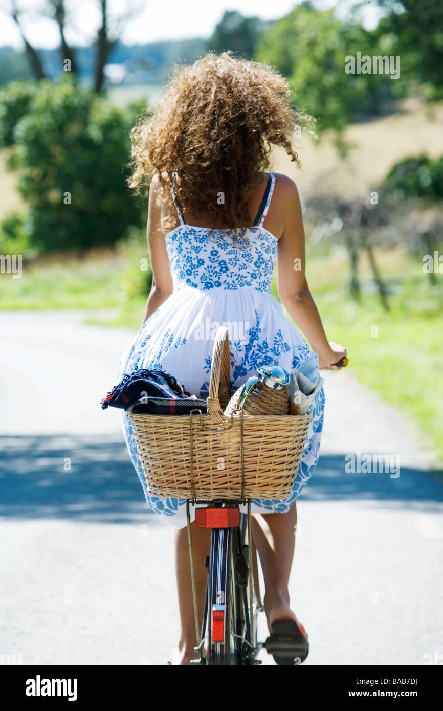 Eine Frau mit dem Fahrrad auf einer Landstraße, Schweden. Stockbild
