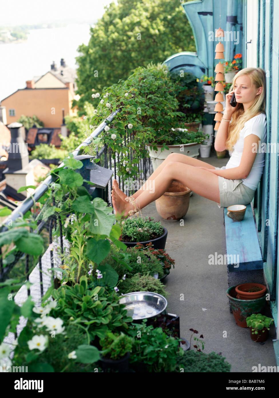 Ein junges Mädchen sitzt auf einem Balkon in das Telefon