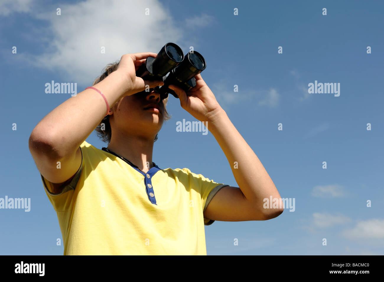 Jungen durch ein Fernglas suchen Stockbild