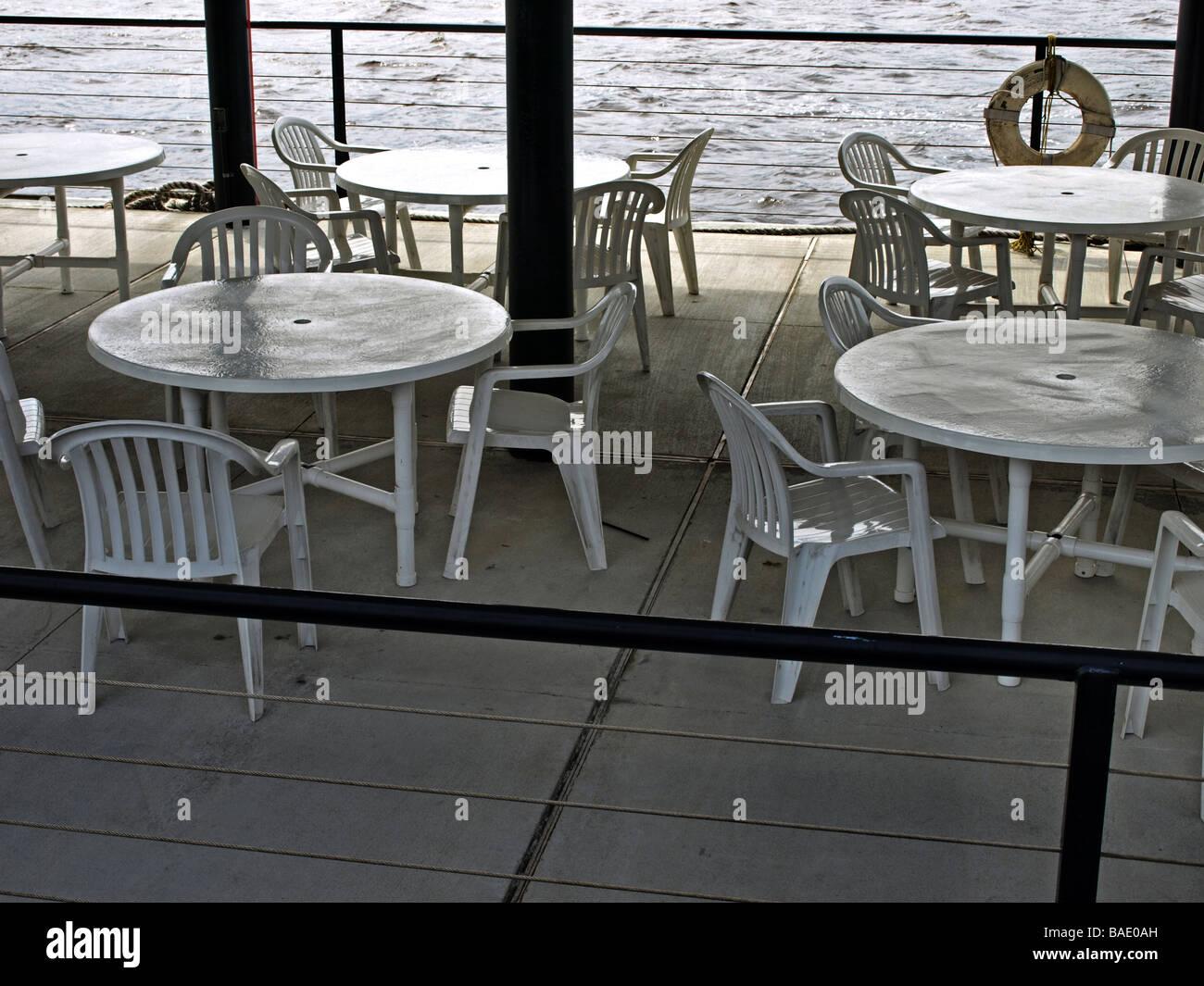 Picknick-Tische und Stühle auf einem Dock nahe dem Fluss weiße ...