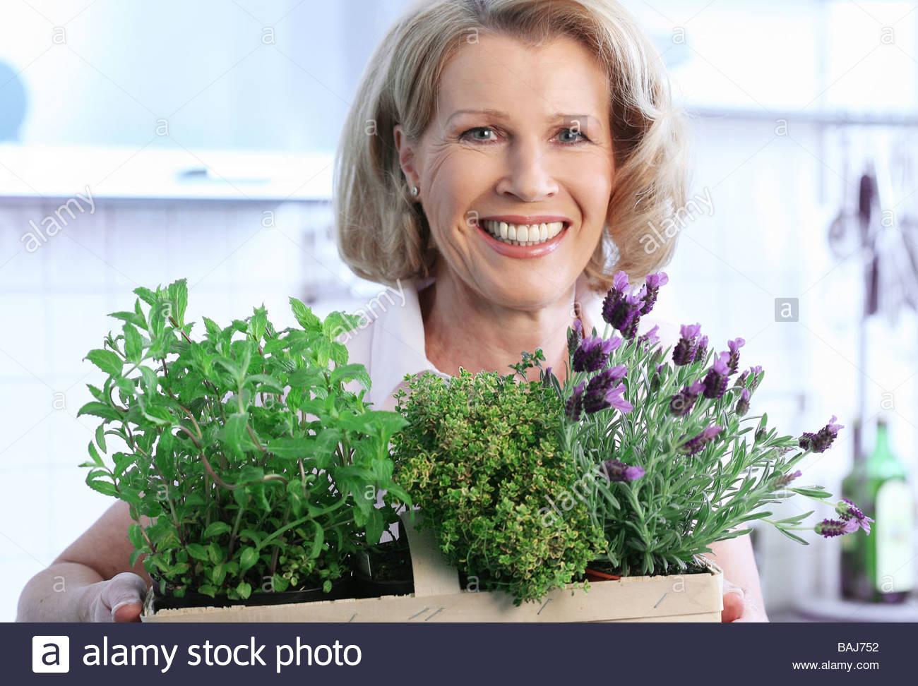 mittlere gealterte Frau hält Korb mit Kräutern in die Hände Stockbild