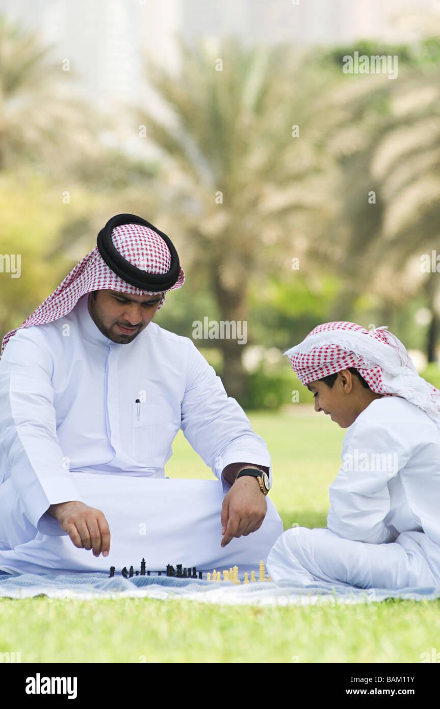Vater und Sohn spielen Schach in einem park Stockbild