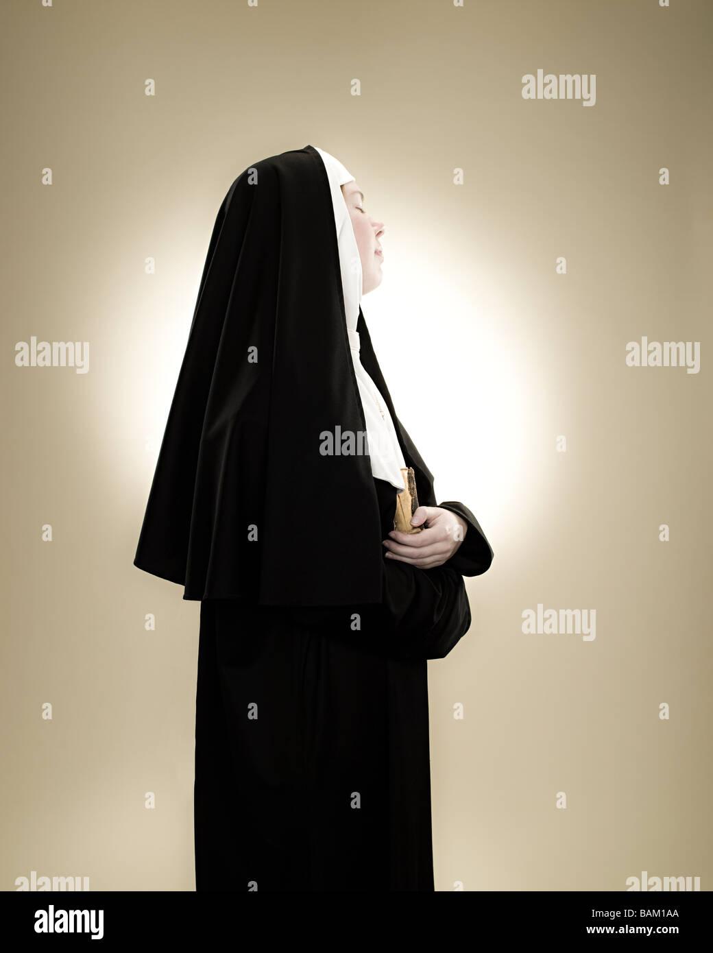 Profil von einer Nonne hält eine Bibel Stockbild