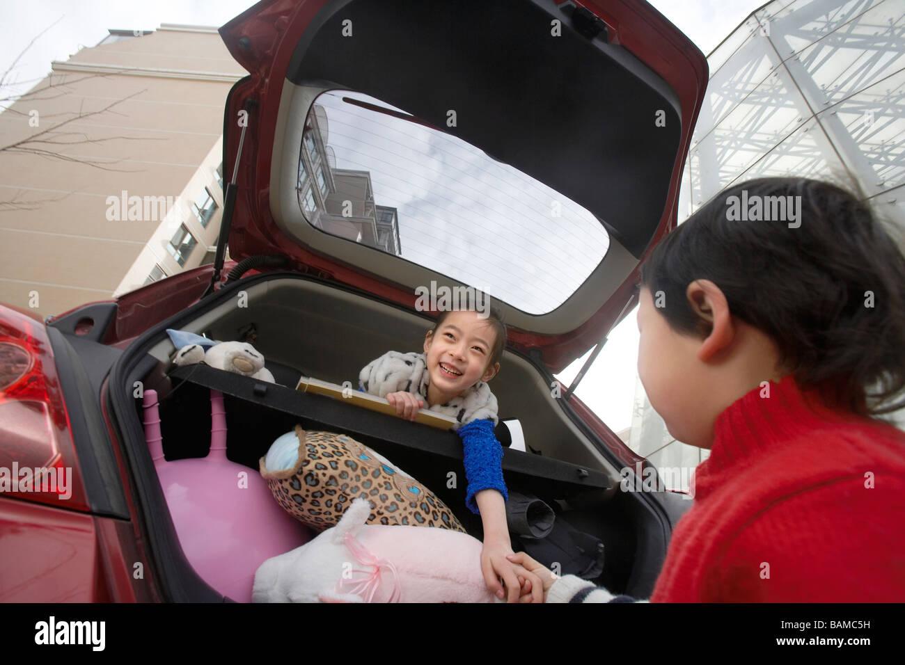 Jungen und Mädchen spielen In und rund um Auto Stockbild