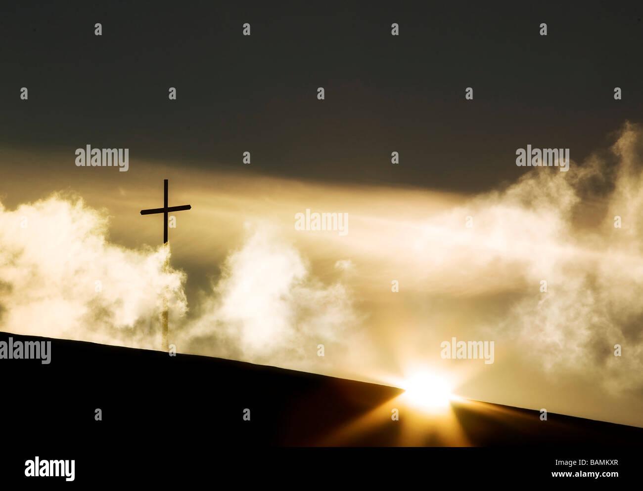 Das Kreuz auf einem Hügel mit dem Sonnenaufgang Stockbild