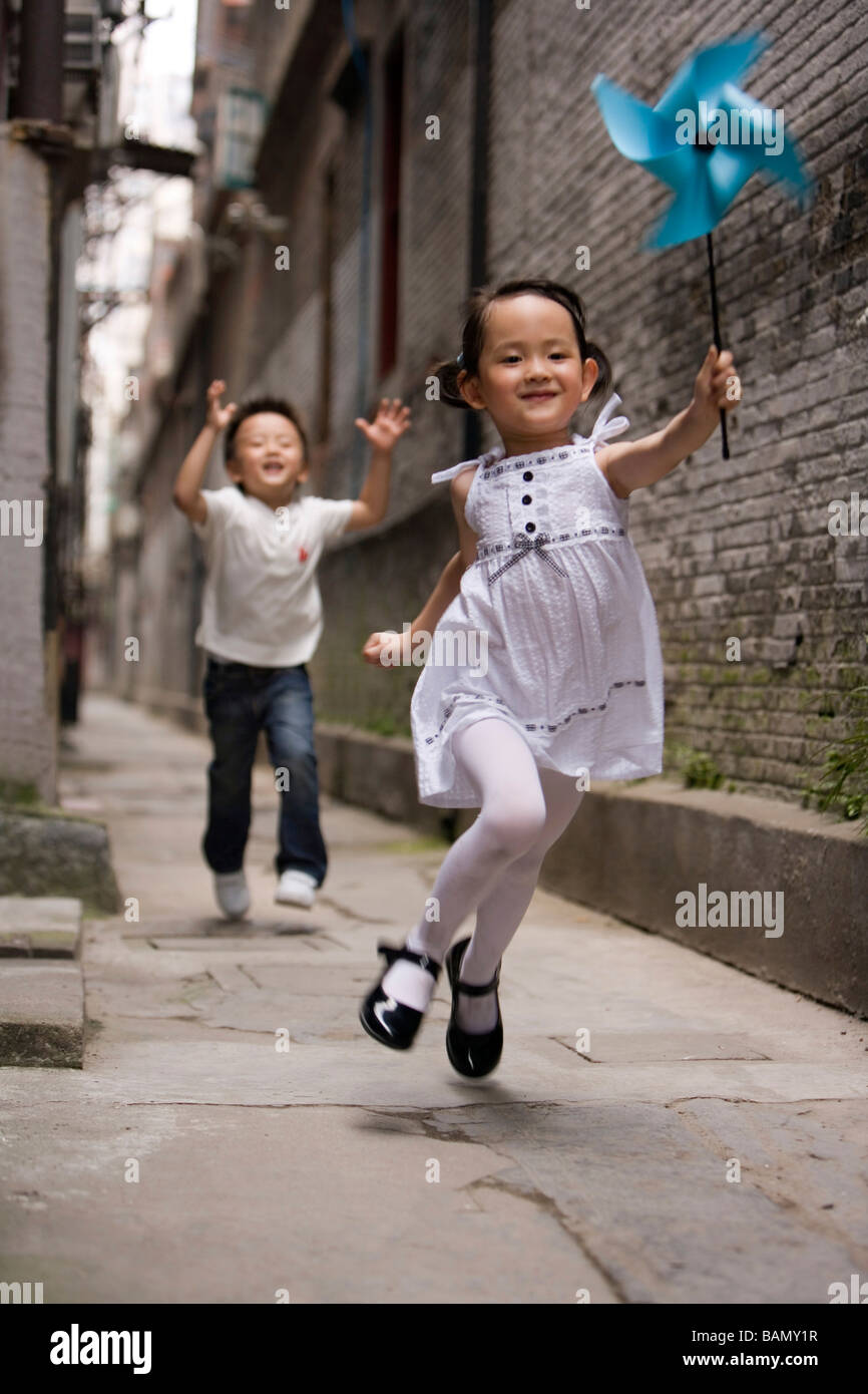 Kinder laufen mit einem Papier-Windrad Stockbild