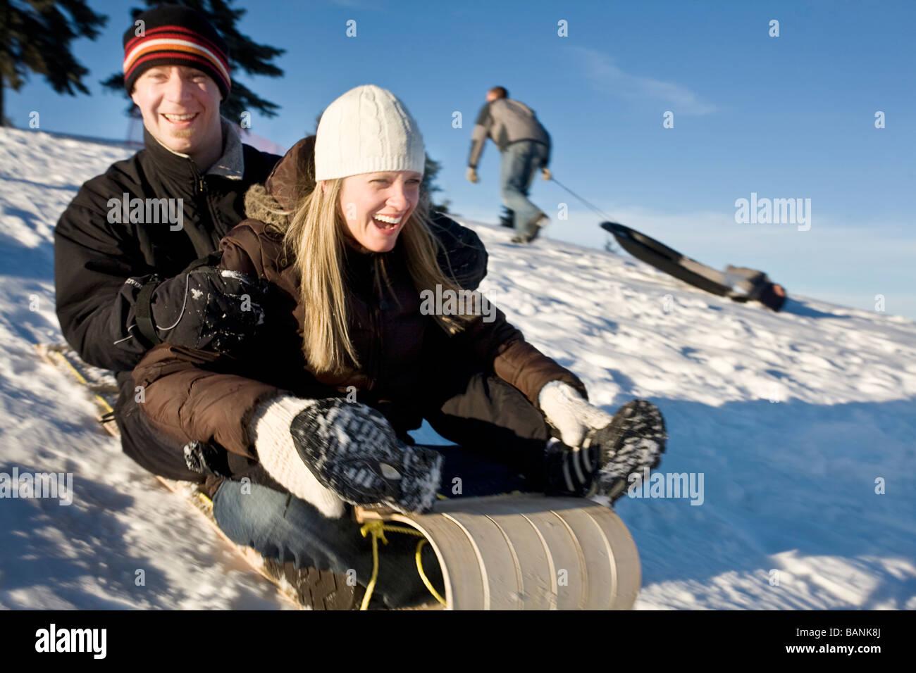 Winter Sport; Paar einen Hügel hinunter rodeln Stockbild