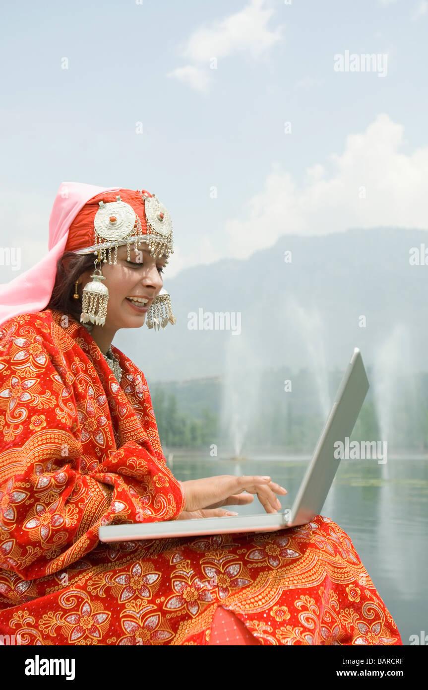 Seitenansicht einer Frau auf einem Laptop arbeiten und lächelnd, Dal Lake, Srinagar, Jammu und Kaschmir, Indien Stockfoto