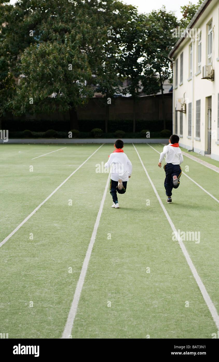 Schülerinnen und Schüler Rennen auf einem Schulhof während einer körperlichen Fitness-Klasse. Stockbild