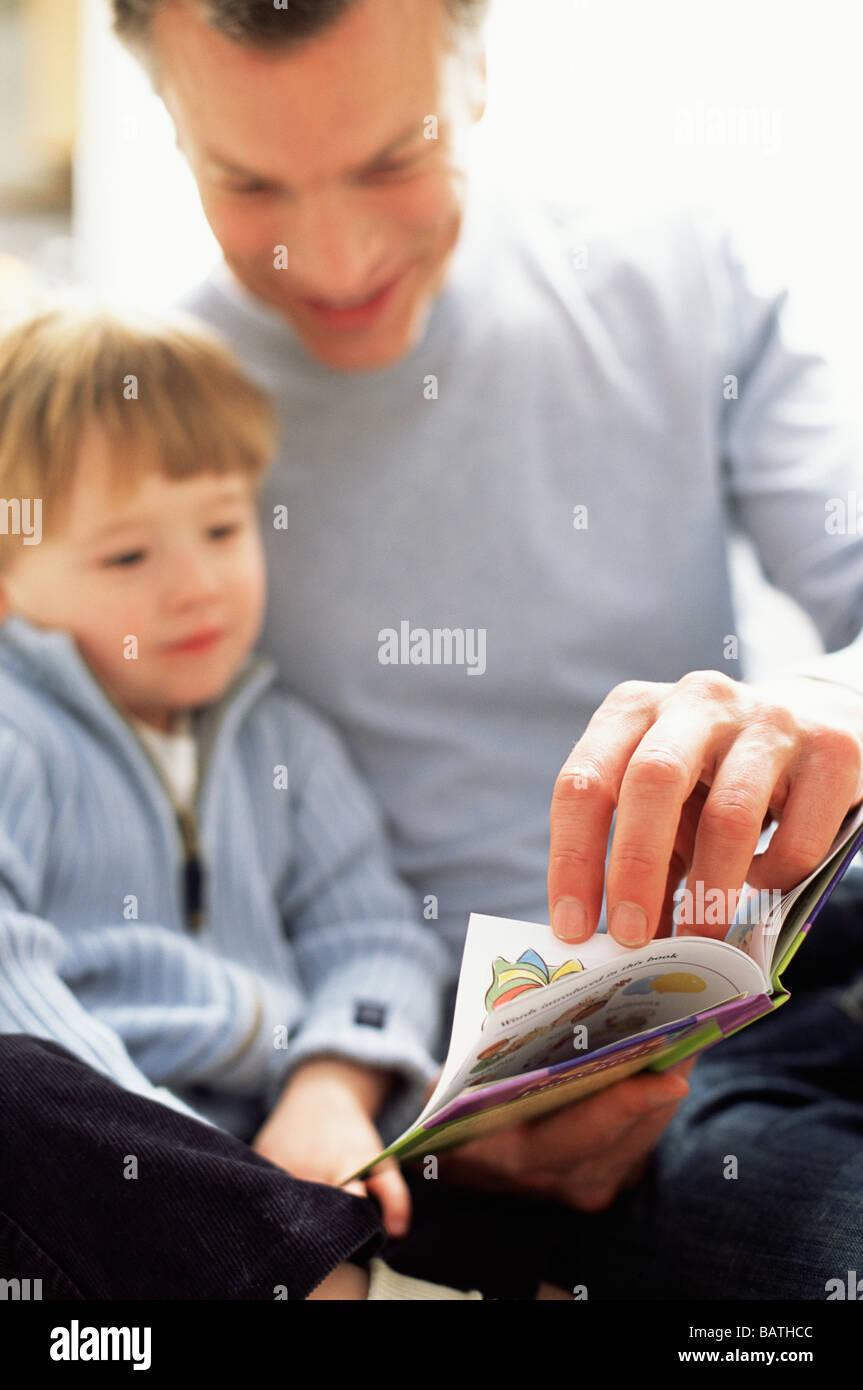 Vaterschaft. Vater mit seinem drei Jahre alten Sohn ein Buch zu lesen. Stockbild
