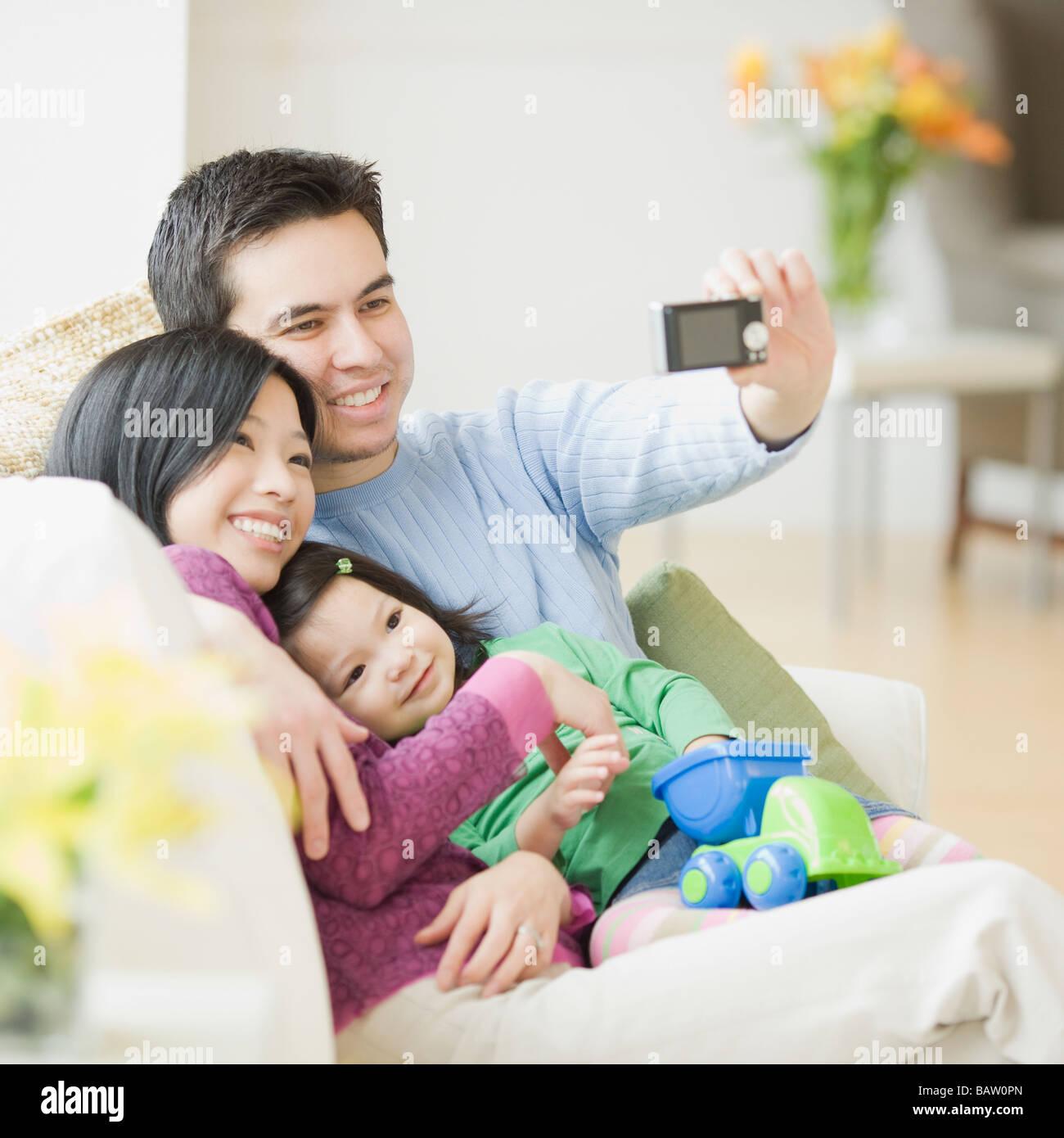 Familie auf der Couch posiert für Fotos Stockfoto