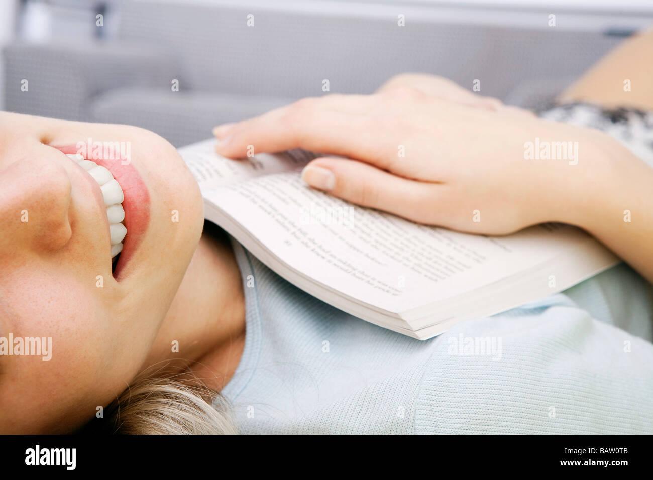 Detail der jungen Frau auf Rücken liegend mit Buch Stockbild