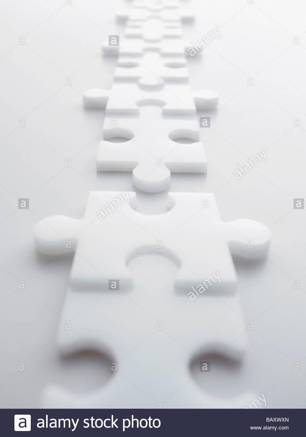 Zwei Linien der getrennten ineinandergreifenden Puzzleteile Stockbild