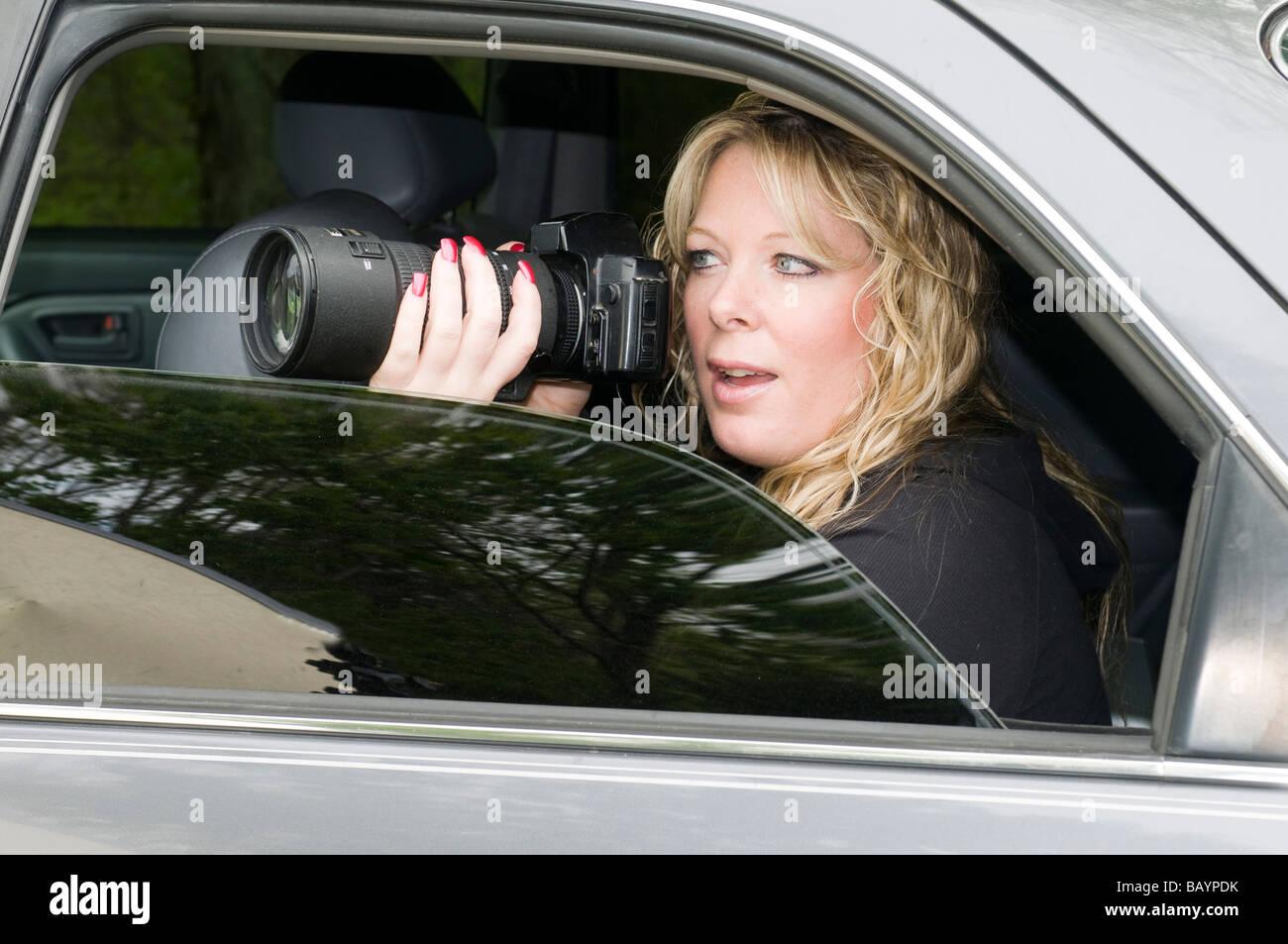 weiblichen Privatdetektiv oder Spion oder Geheimagenten fotografieren aus dem Auto Stockbild