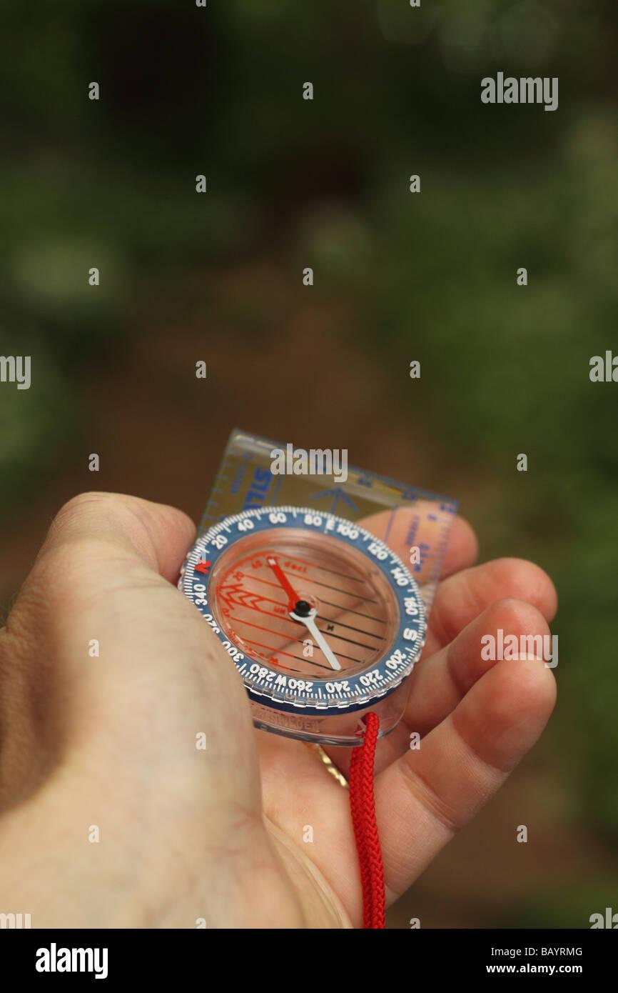 Hand hält einen Kompass, Richtung Lager und in einem Wald in Richtung zu finden Stockbild
