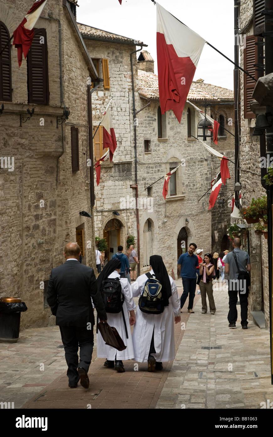 Nonnen und Geschäftsmann auf Straße in Assisi unter Flaggen Stockbild