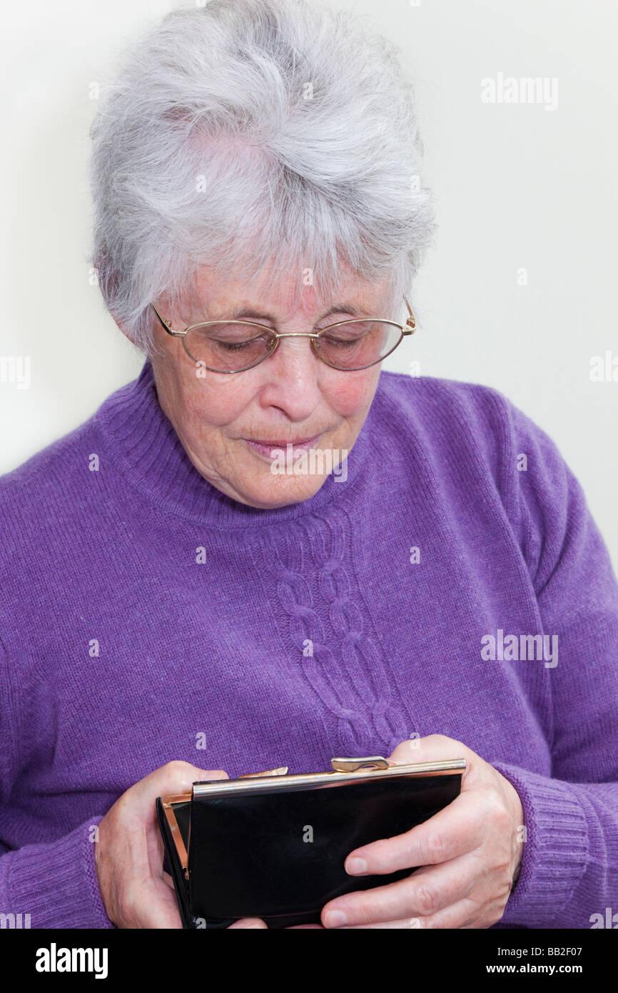 Nahaufnahme eines mittellosen britische Rentner sucht in einem leeren Geldbeutel in ihre Hände mit den betroffenen Stockbild