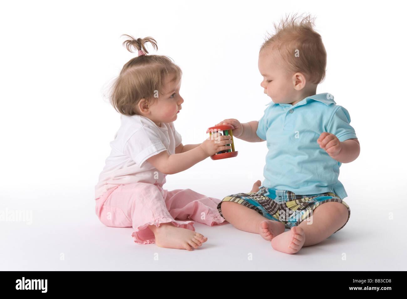 Zwei Kleinkinder spielen mit einem Spielzeug Stockbild