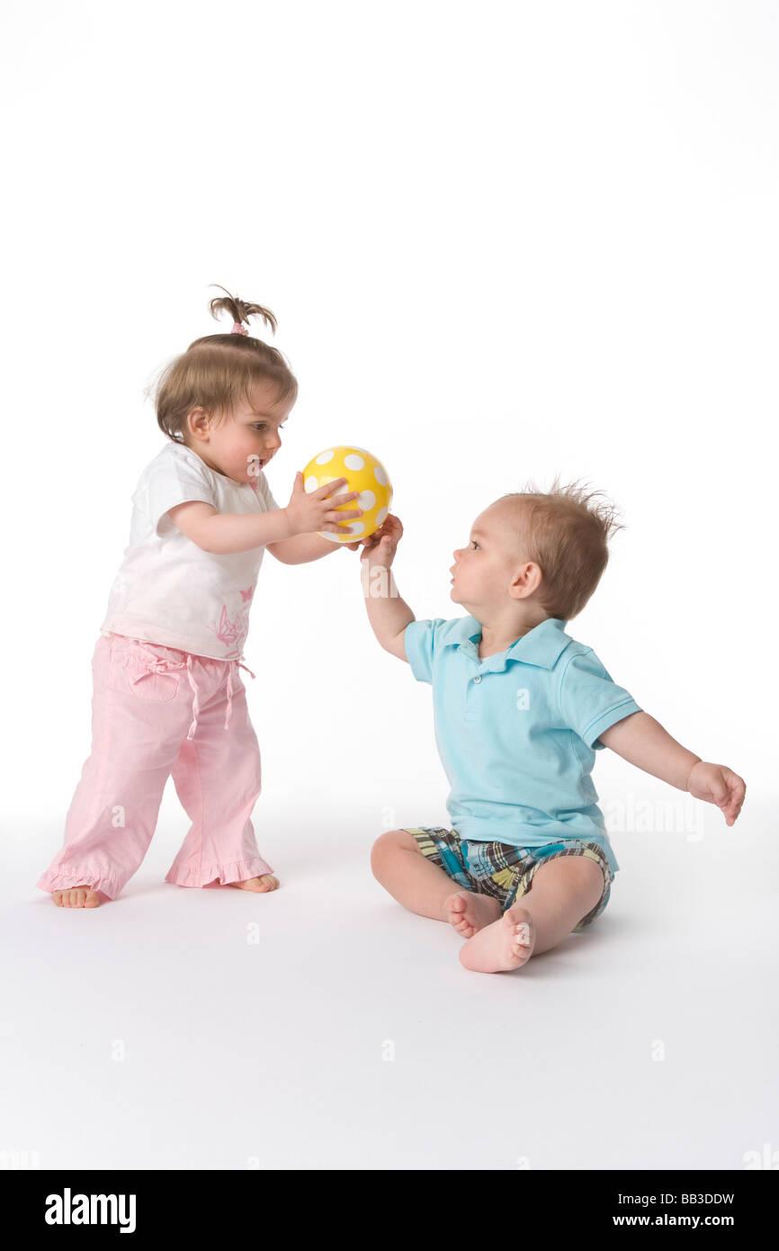 Zwei Kleinkinder spielen mit einem ball Stockbild