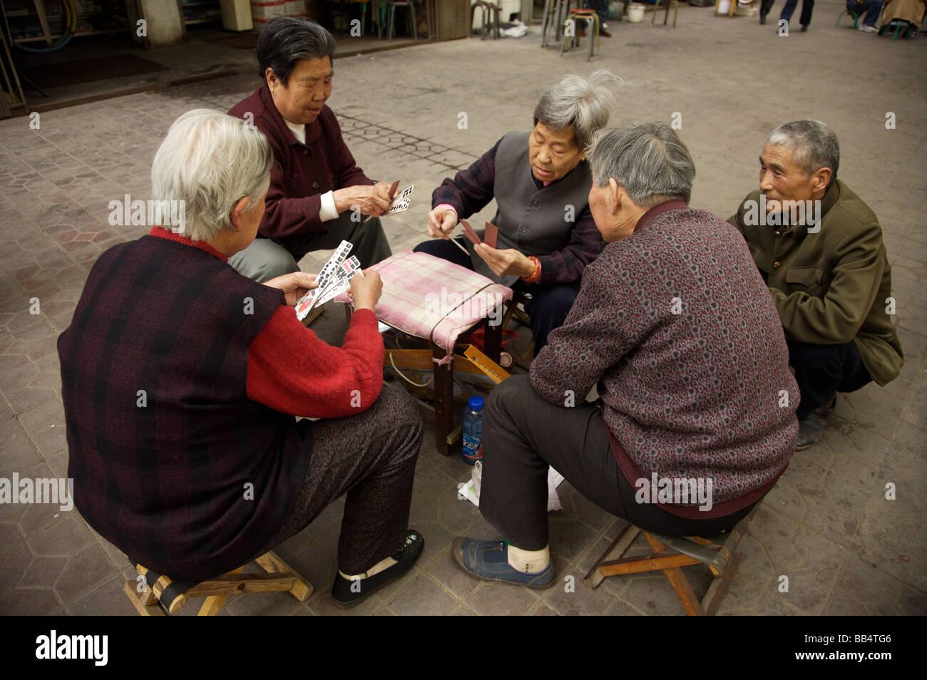 Einheimische spielen chinesische Kartenspiel auf der Straße Stockbild