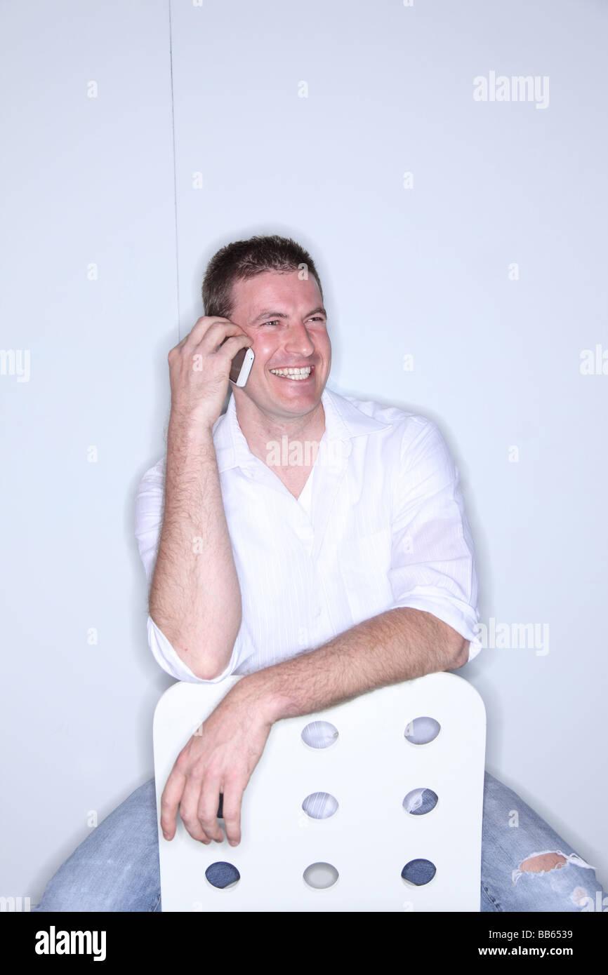 Mann sitzt in moderner Stuhl mit Handy lachen Stockbild
