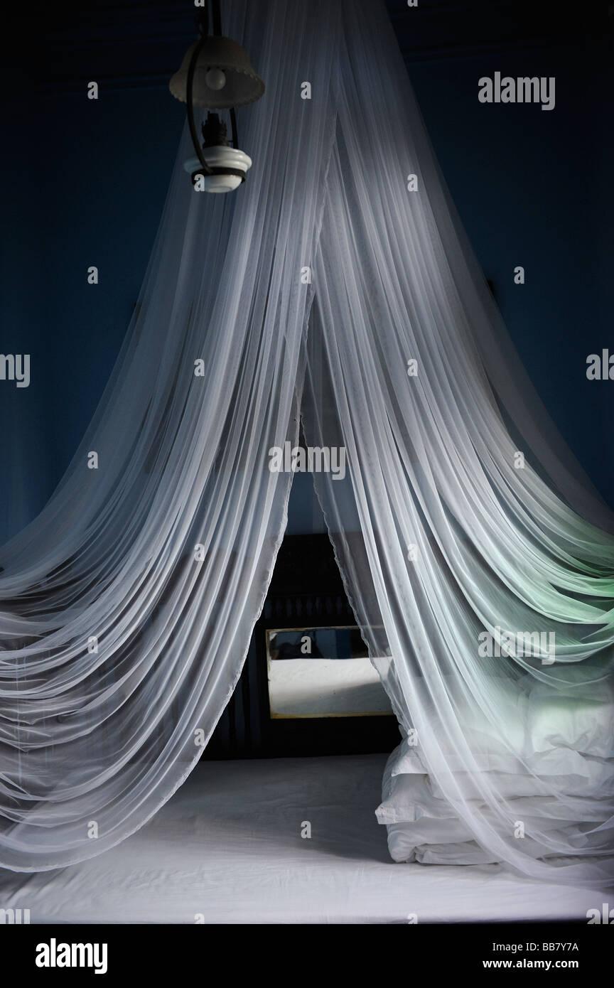 Weißes Moskitonetz über dem Bett in einem Hotel. Stockbild