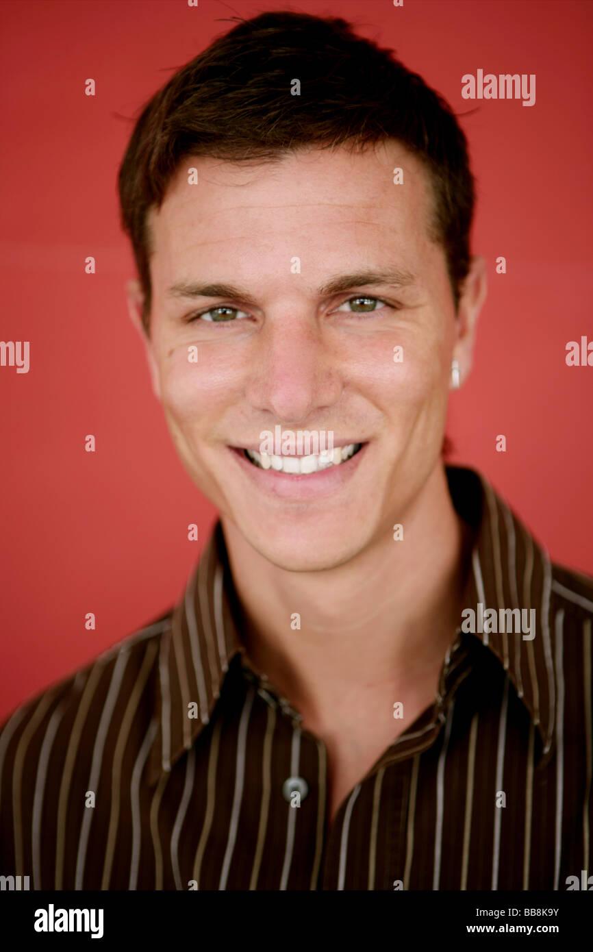 Porträt des jungen glücklich und sanfte lächelnder Mann Stockbild