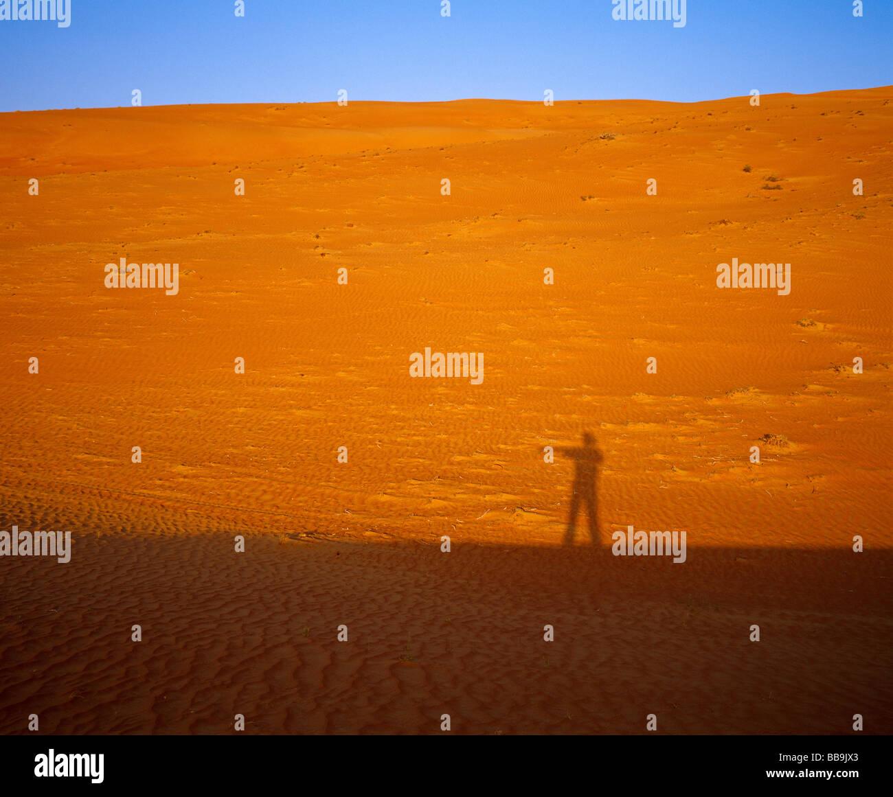 Schatten von einem Mann deutete die Richtung bei Sonnenuntergang in der Wüste Wahiba Sands Sharquiya Stockbild
