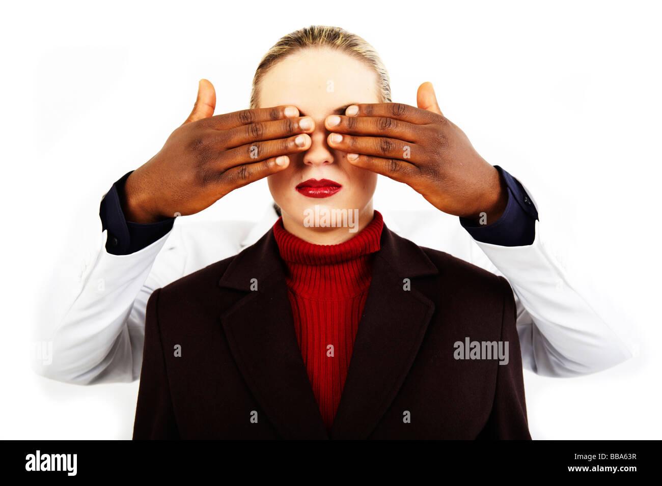 Dunkel-enthäutete Hände, die Augen eines jungen blonden Mädchens zu halten geschlossen Stockbild