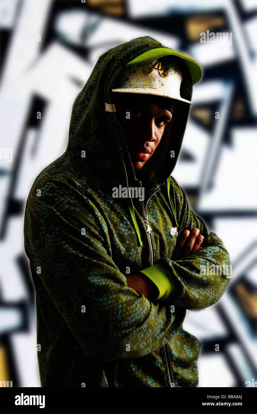 Dunkelhäutige junge Mann in ein Rapper-Outfit vor Graffitiwand Stockbild