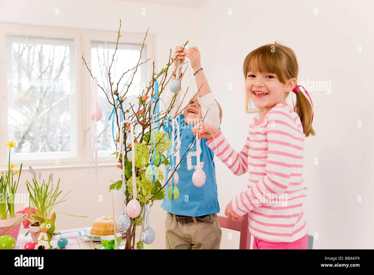 Mädchen und jungen schmücken Ostertisch Stockfoto