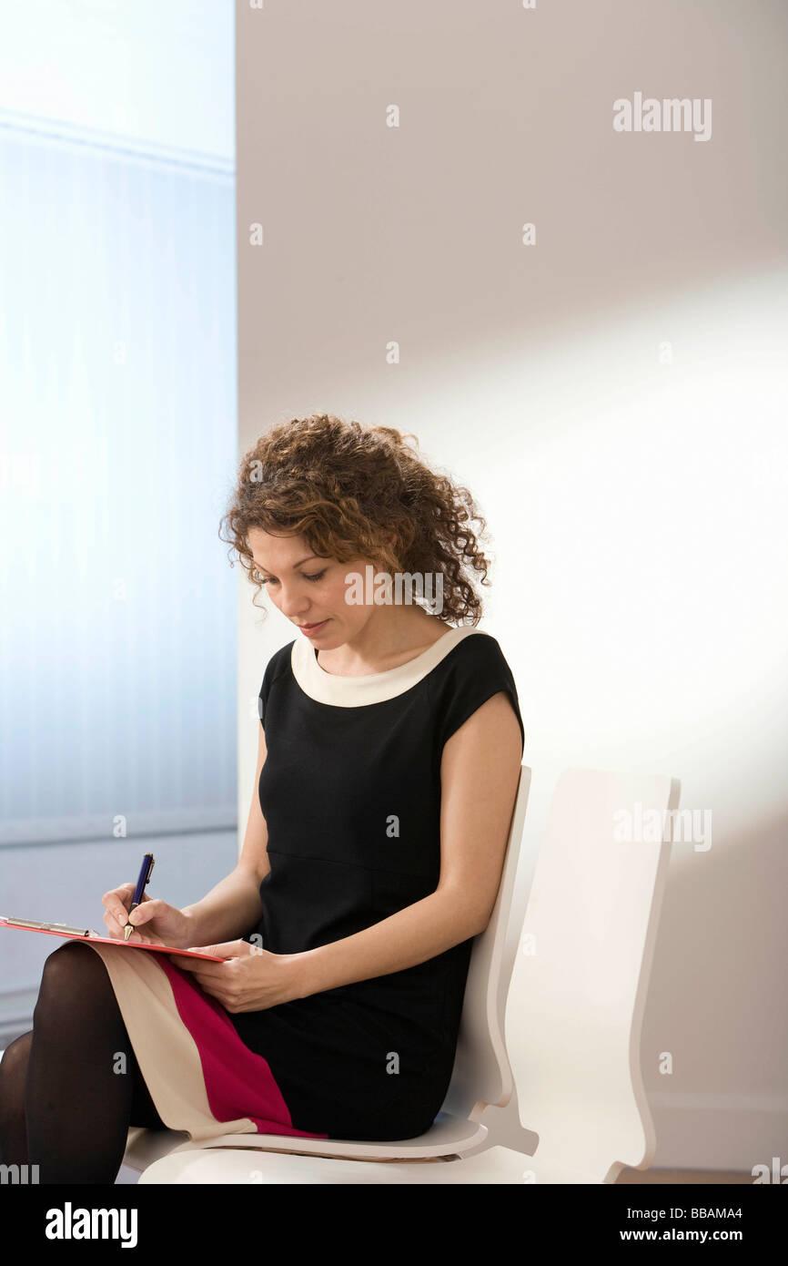 Ein Weibchen, das Ausfüllen eines Formulars Stockbild