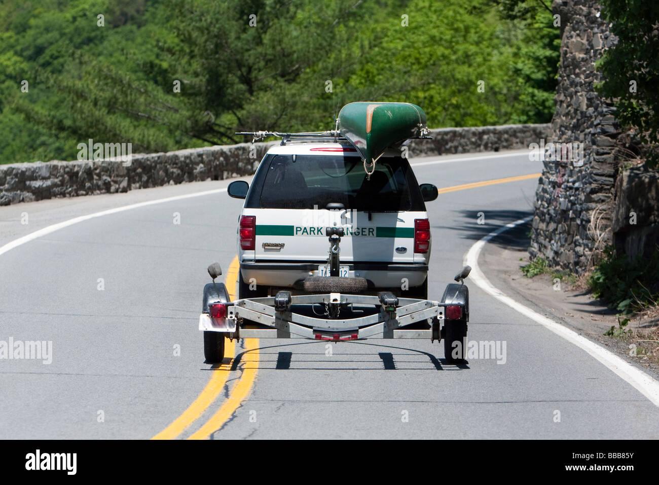 Ein Park Ranger LKW auf einer kurvenreichen Straße, mit dem Kanu auf einem Dachgepäckträger und einen Stockbild