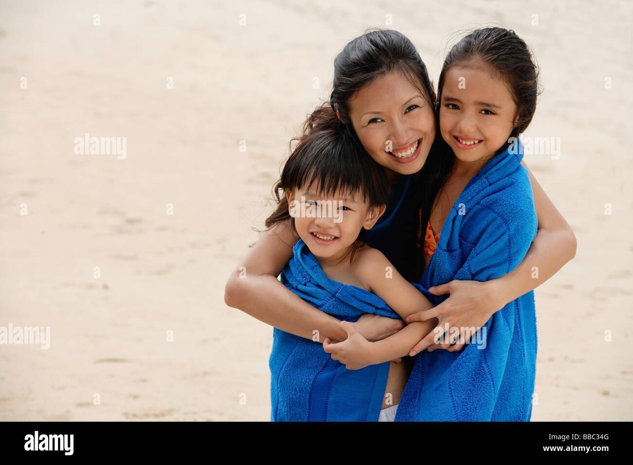 Mutter, Sohn und Tochter am Strand, Kinder in blauen Handtuch ...